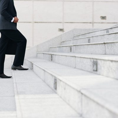 Cropped image of businessman walking up the stairs